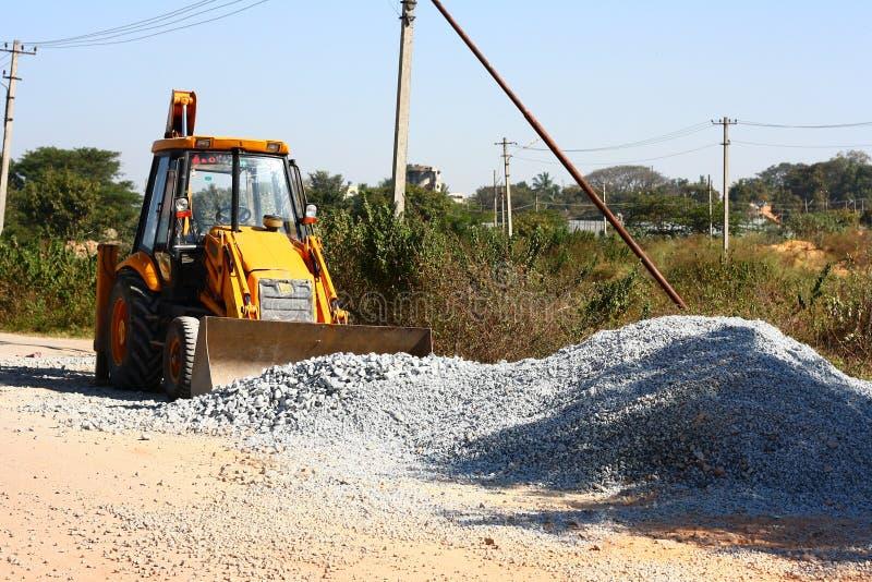 Carregador amarelo do Backhoe na construção de estradas fotografia de stock royalty free