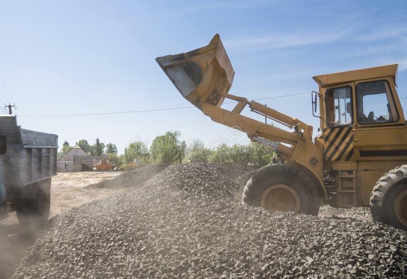 Carregador amarelo que entrega o cascalho de pedra no caminhão durante trabalhos de construção de estradas As pedras para a estra imagens de stock