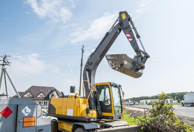 Carregador de máquina escavadora amarelo que está contra o céu nebuloso ensolarado durante a construção de estradas e que repara  fotografia de stock royalty free