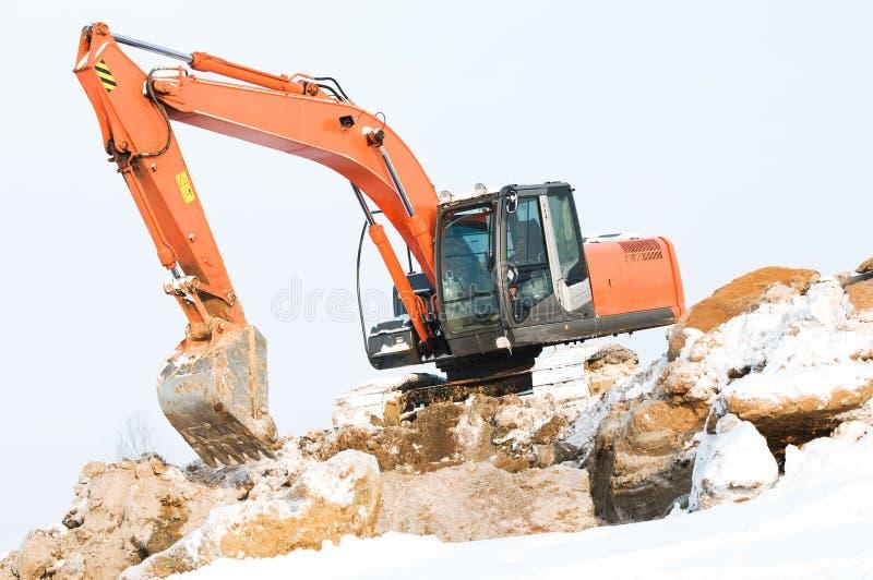 Carregador de máquina escavadora em trabalhos do inverno foto de stock
