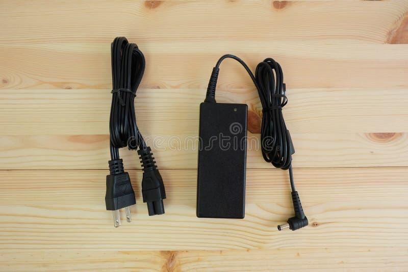 Carregador do poder do adaptador ac/dc com fio do laptop em de madeira imagens de stock