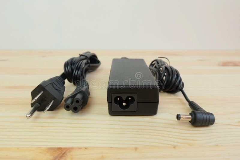 Carregador do poder do adaptador ac/dc com fio do laptop em de madeira imagem de stock royalty free