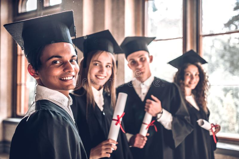 Carreiras bem sucedidas - aqui nós vimos! Grupo de graduados de faculdade de sorriso que estão junto na universidade e que sorrie fotografia de stock royalty free