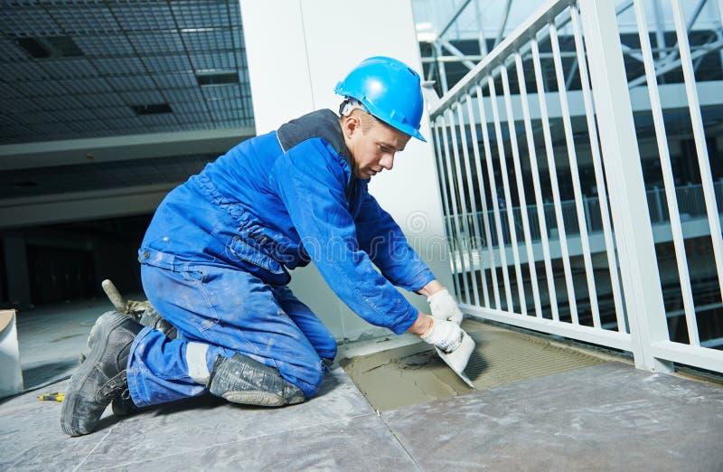Carreleur à la construction ou à la rénovation industrielle de carrelage de plancher image stock