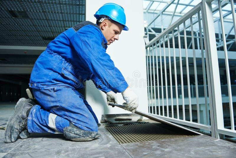 Carreleur à la rénovation industrielle de carrelage de plancher images libres de droits