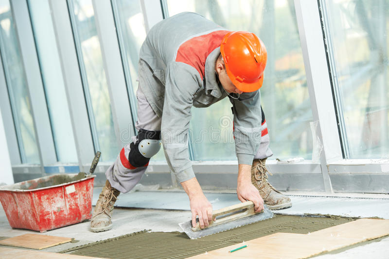 Carreleur au travail de rénovation industriel de carrelage de plancher photographie stock