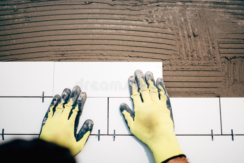 Carreleur industriel, tenant et installant les tuiles en céramique de salle de bains pendant la rénovation photographie stock libre de droits