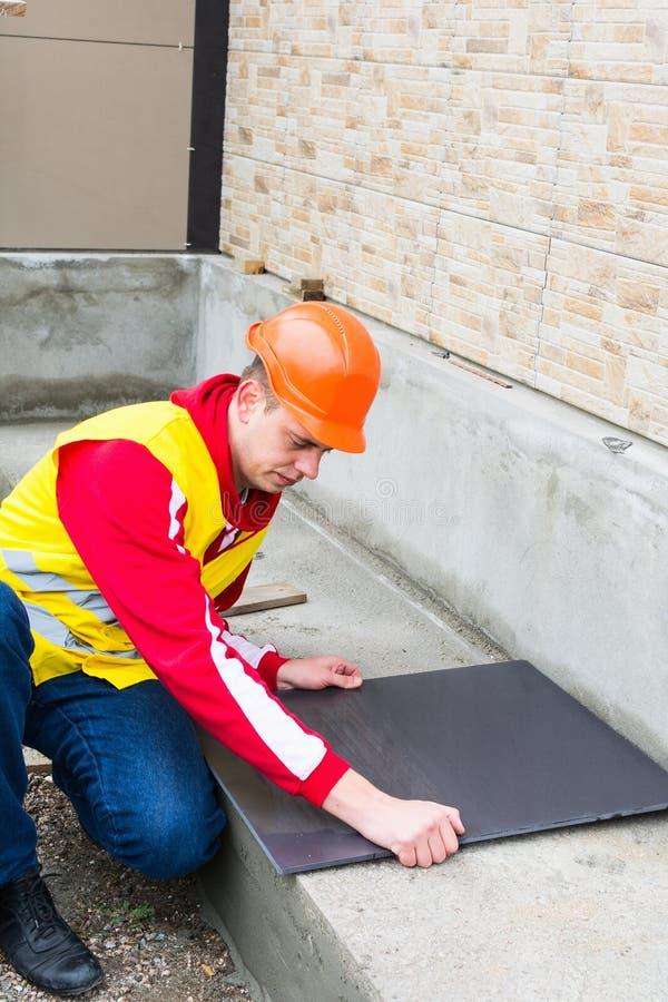 Carreleur installant les carreaux de céramique image libre de droits