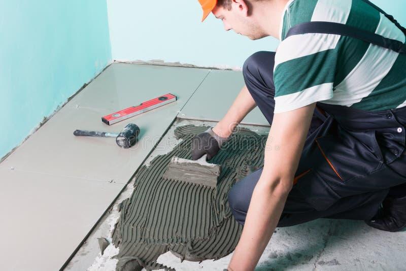 Carreleur installant les carreaux de céramique photo libre de droits