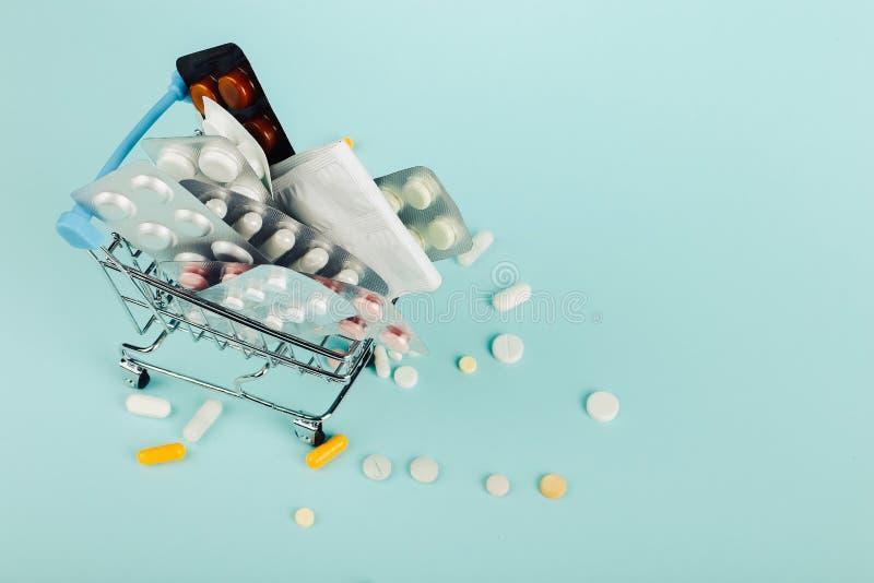 Carrello caricato con le pillole su un fondo blu Il concetto di medicina e la vendita delle droghe Copi lo spazio fotografia stock libera da diritti