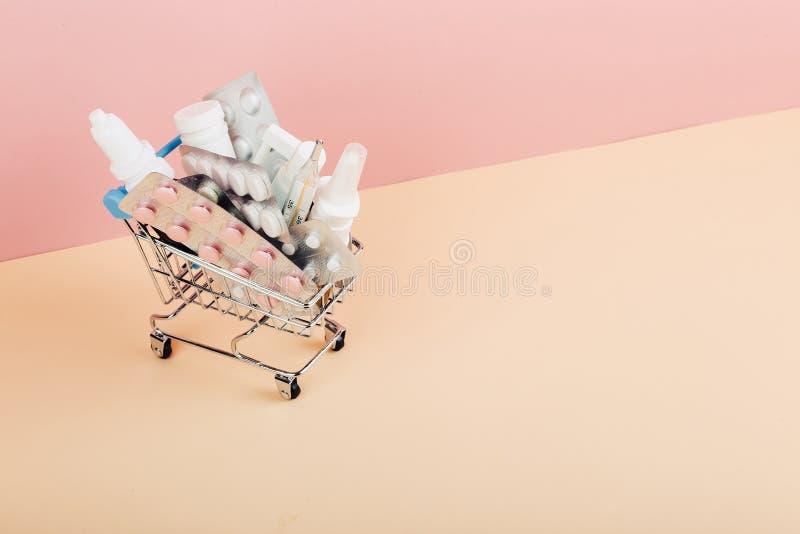 Carrello caricato con le pillole su un fondo giallo rosa Il concetto di medicina e la vendita delle droghe Copi lo spazio fotografia stock