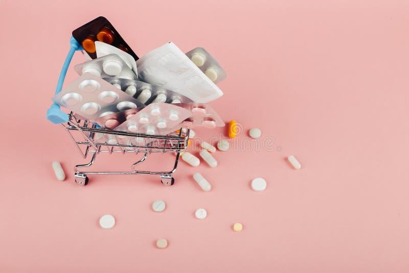 Carrello caricato con le pillole su un fondo rosa Il concetto di medicina e la vendita delle droghe Copi lo spazio immagini stock