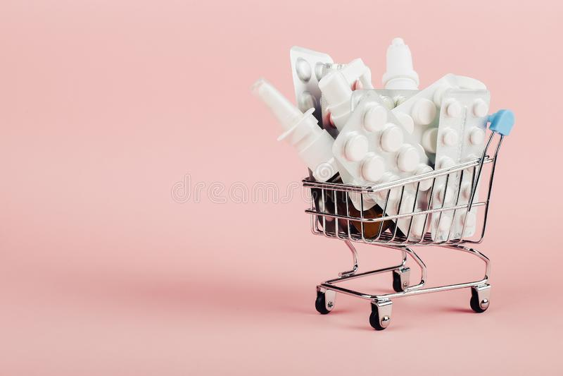 Carrello caricato con le pillole su un fondo rosa Il concetto di medicina e la vendita delle droghe Copi lo spazio fotografia stock