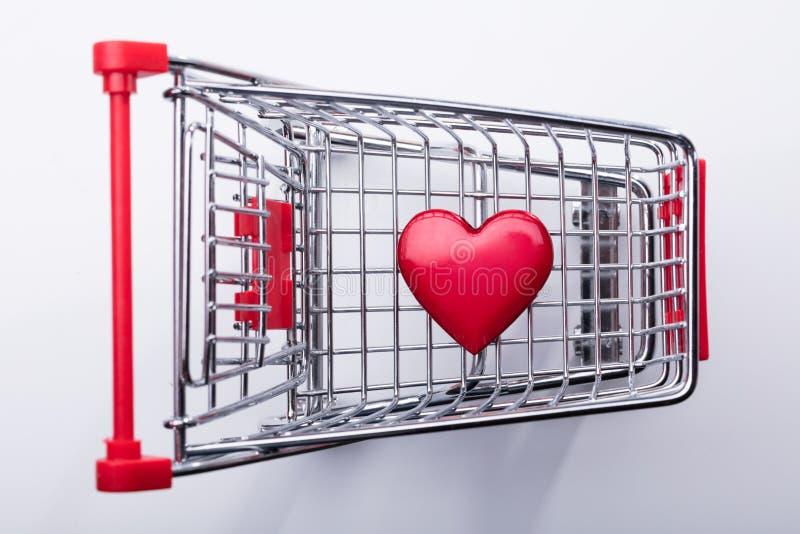 Carrello con cuore rosso immagine stock