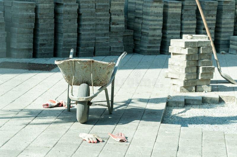 Carrello della costruzione con i guanti dei lavoratori e pietra della pavimentazione nei precedenti sulla via che pavimenta sito immagine stock libera da diritti