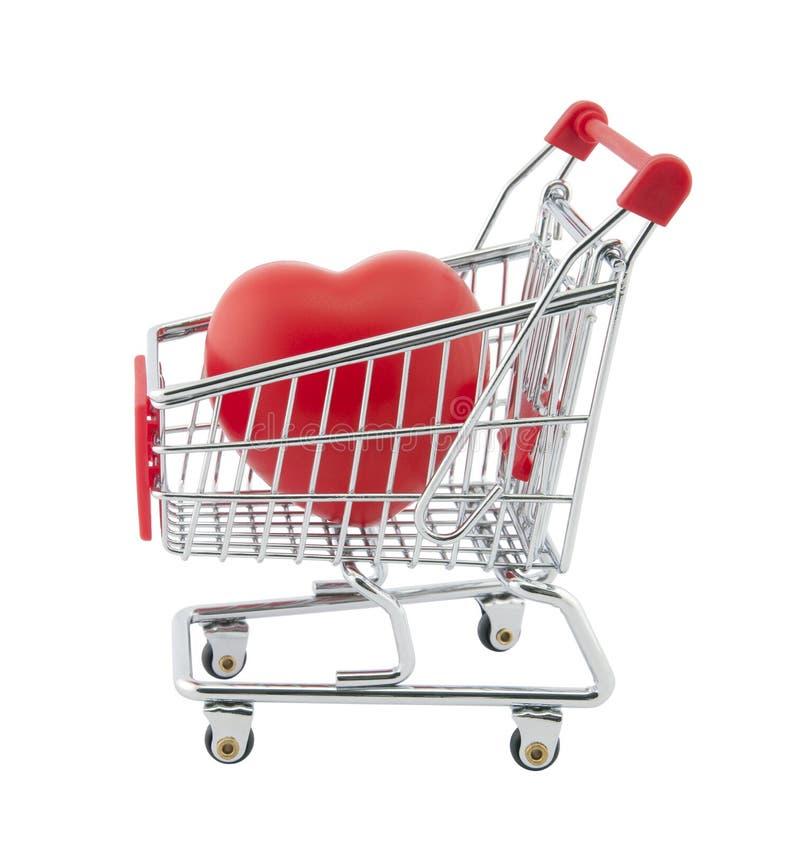 Carrello di acquisto e cuore rosso. Il percorso di residuo della potatura meccanica include fotografia stock libera da diritti