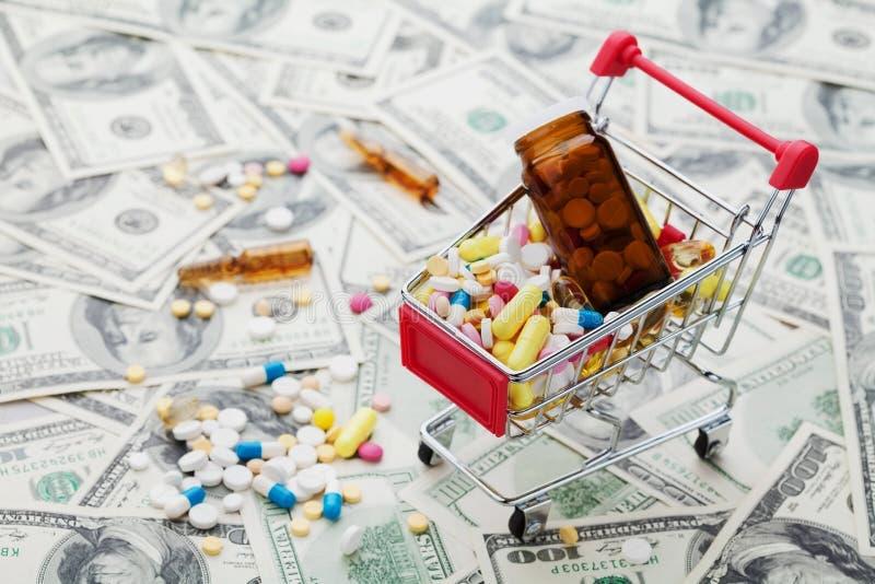 Carrello in pieno delle pillole della medicina e della droga sul fondo dei soldi del dollaro fotografie stock