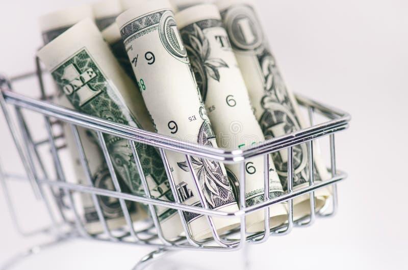 Carrello pieno di acquisto con le banconote del dollaro su un fondo bianco Isolato Concetto di consumismo e di soldi immagini stock