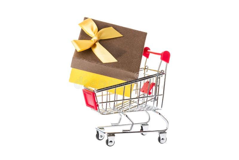 Carrello rosso del carrello con un giftbox isolato su fondo bianco Concetto di acquisto fotografia stock libera da diritti