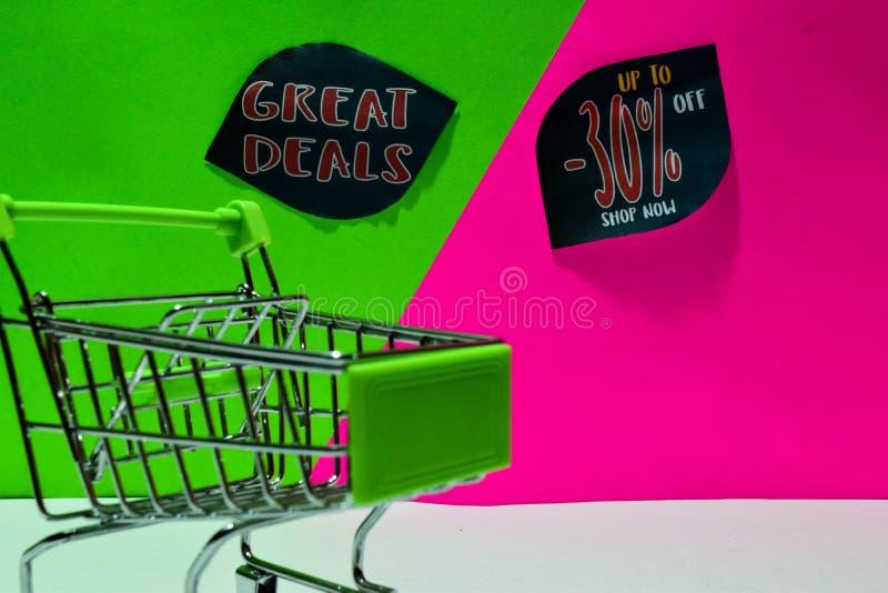 Carrello verde grandi affari allegati e fino a 30% fuori dal testo del negozio ora su fondo verde e rosa fotografie stock libere da diritti