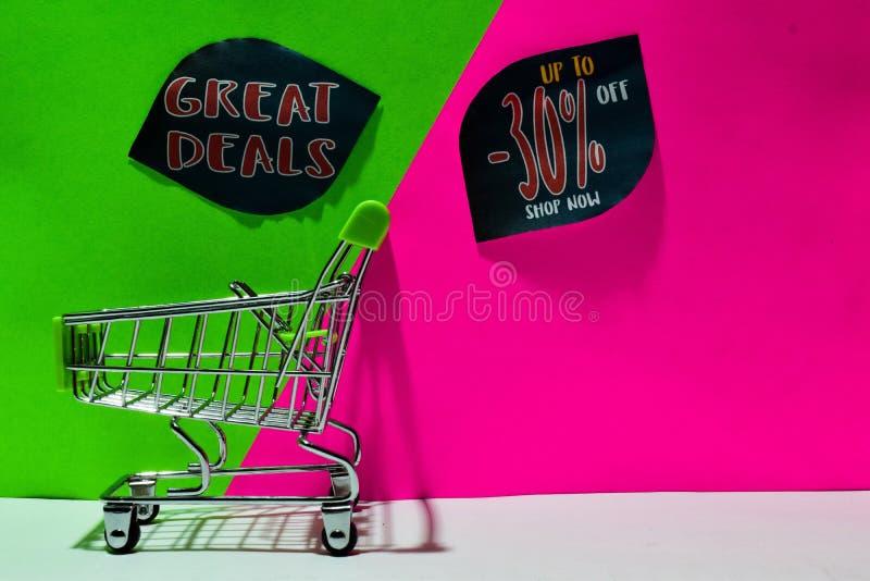 Carrello verde grandi affari allegati e fino a 30% fuori dal testo del negozio ora su fondo verde e rosa immagini stock libere da diritti