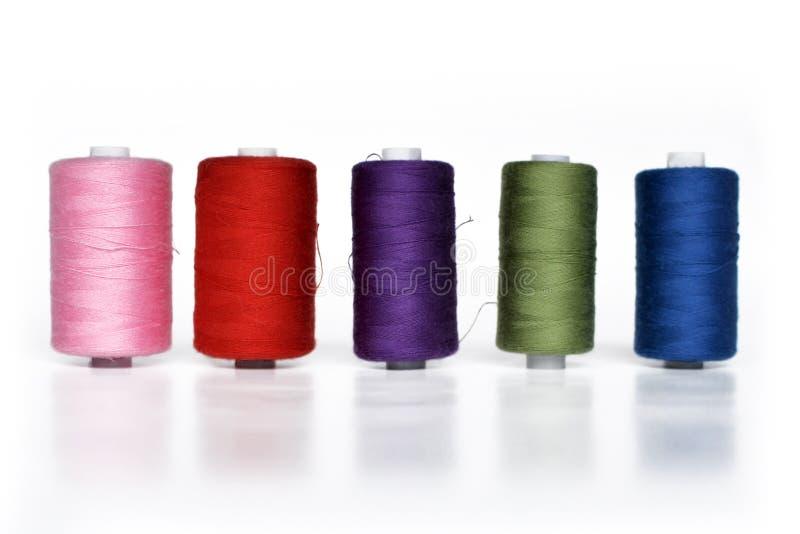 Carretéis coloridos diferentes com o fio da costura em seguido isolado no fundo branco imagem de stock