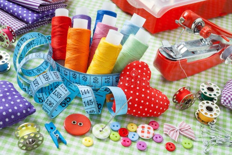 Carretéis da linha colorida, botões, telas, fita de medição, pino fotos de stock royalty free