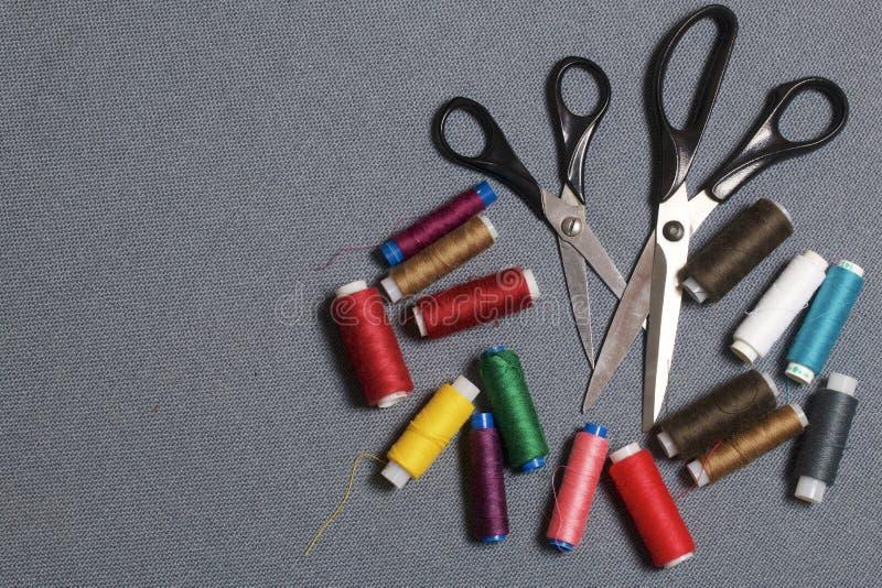Carretéis das linhas de cores diferentes em um fundo tecido cinzento Dois pares de tesouras de tamanhos diferentes imagem de stock