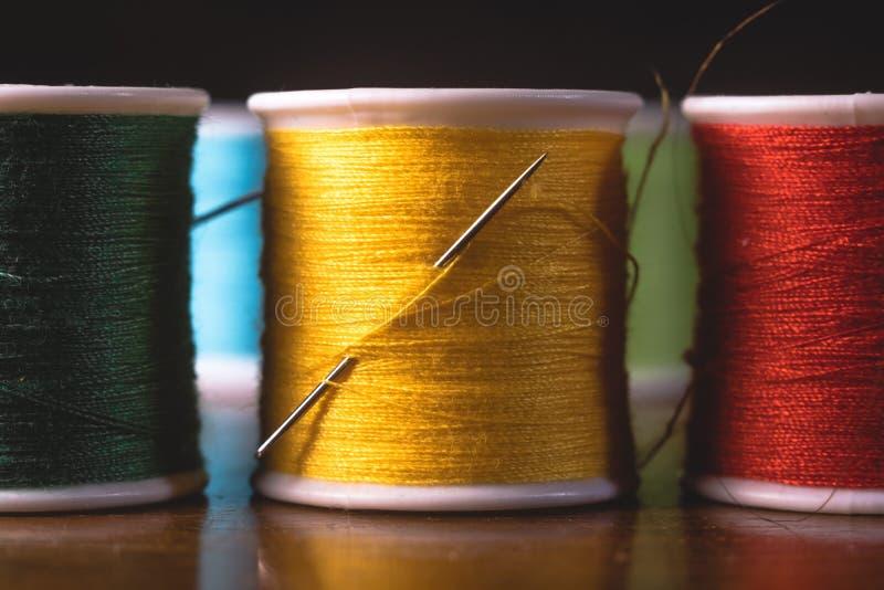 Carretéis vívidos borrados das bobinas das linhas das cores, projeto de conceito costurando industrial fotografia de stock