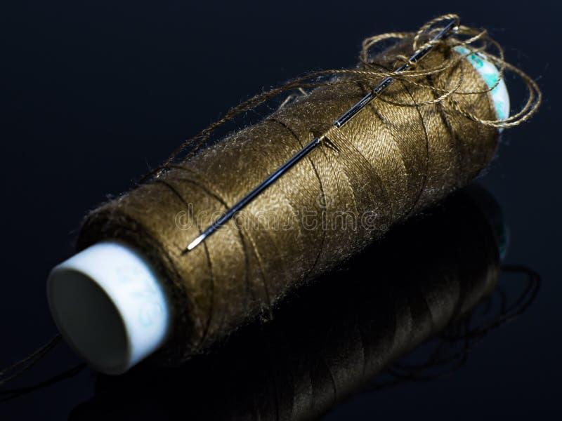 Carrete del hilo de coser con una aguja fotografía de archivo libre de regalías