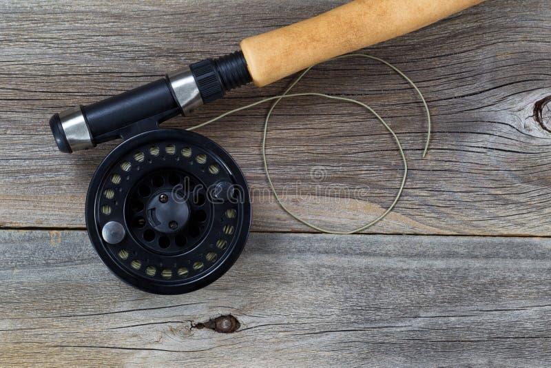 Carrete y línea de la pesca con mosca en la madera rústica fotos de archivo