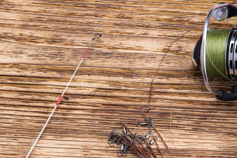 Carretel com linha de pesca das mentiras do polo de pesca em um fundo queimado de madeira fotografia de stock royalty free