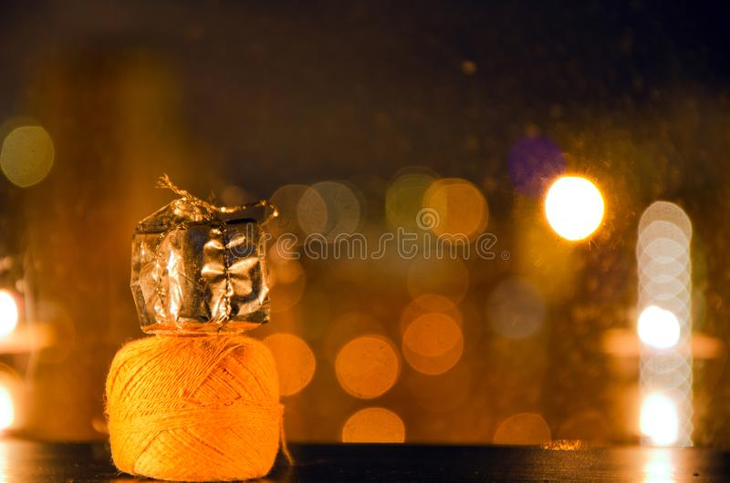Carretel da linha e de um presente do Natal no fundo com luzes obscuras fotos de stock