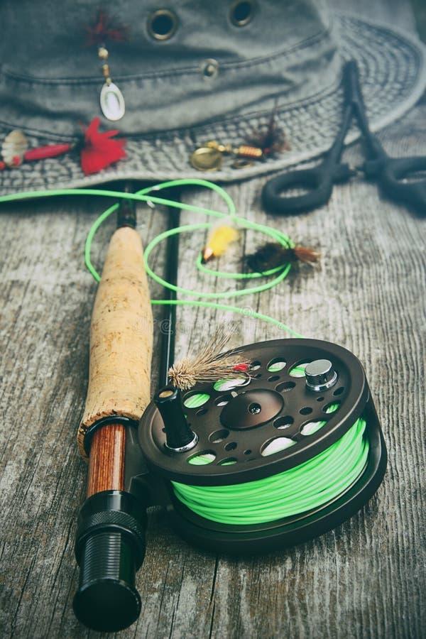 Carretel da pesca com mosca com o velho chapéu no banco fotografia de stock royalty free