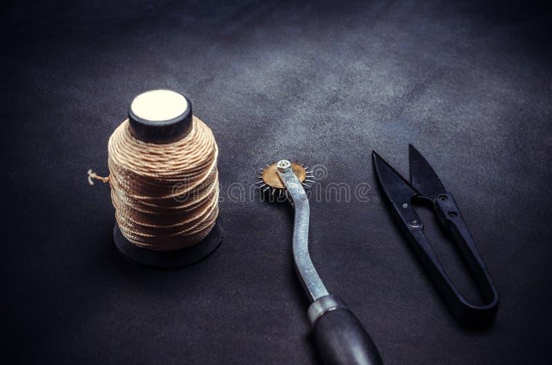 Carretel de linhas e de ferramentas do amarelo no fundo preto imagem de stock royalty free