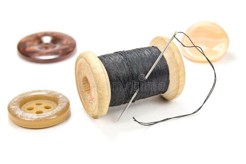 Carretel de madeira do vintage da linha, da agulha e de botões pretos no fundo branco fotografia de stock