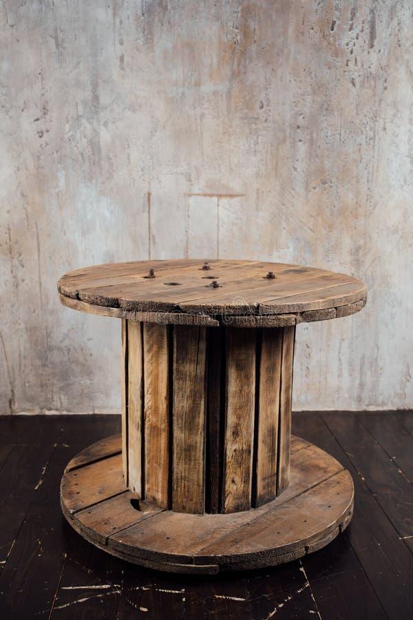 Carretel de madeira velho contra o fundo do muro de cimento foto de stock royalty free