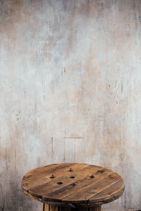 Carretel de madeira velho contra o fundo do muro de cimento fotografia de stock royalty free