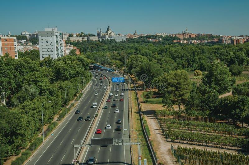 Carretera con la circulación densa y árboles en Madrid imagenes de archivo