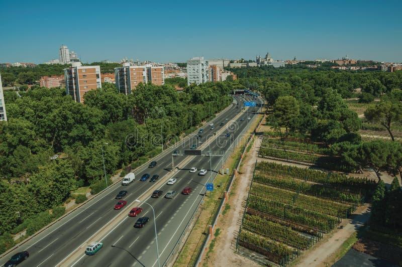 Carretera con la circulación densa y árboles en Madrid foto de archivo