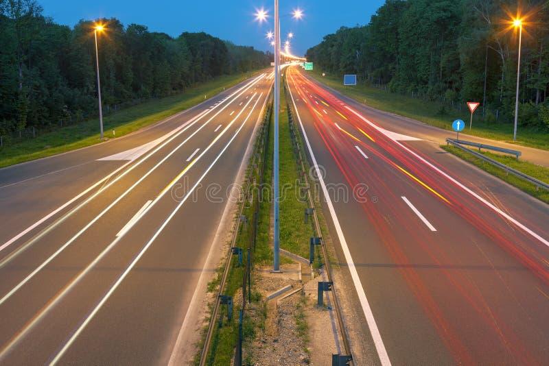 Carretera con los rastros de la luz en la oscuridad fotos de archivo