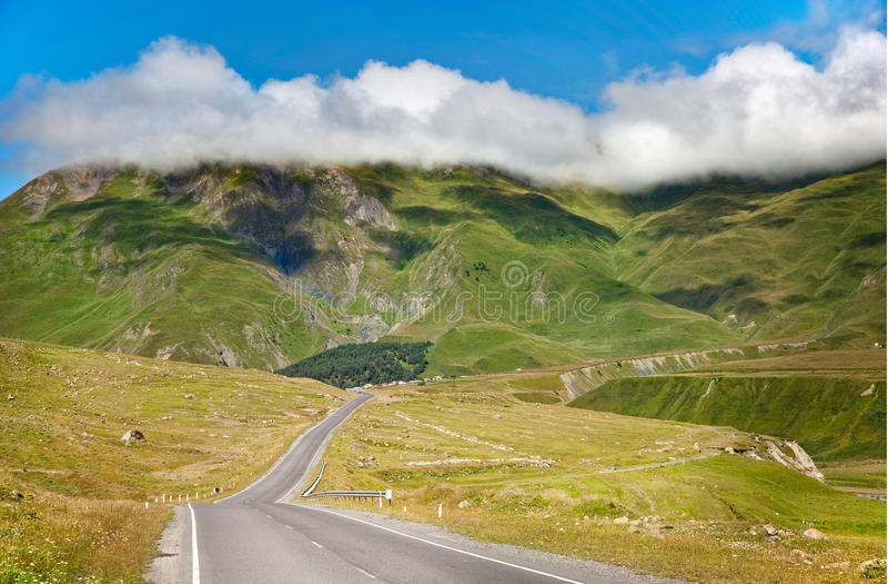 Carretera de asfalto con el cielo nublado y la luz del sol imagen de archivo