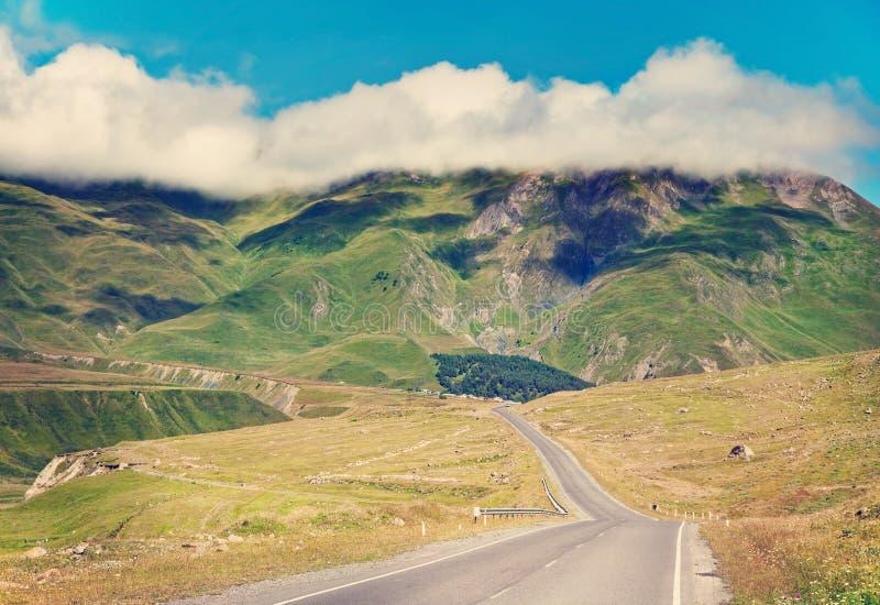 Carretera de asfalto con el cielo nublado y la luz del sol fotografía de archivo