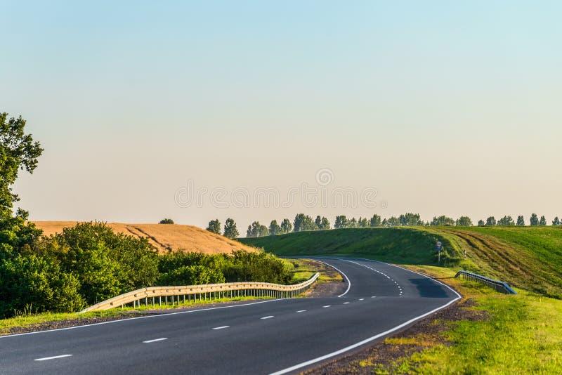 Carretera de asfalto del campo con los carriles de la marca y de guardia fotografía de archivo