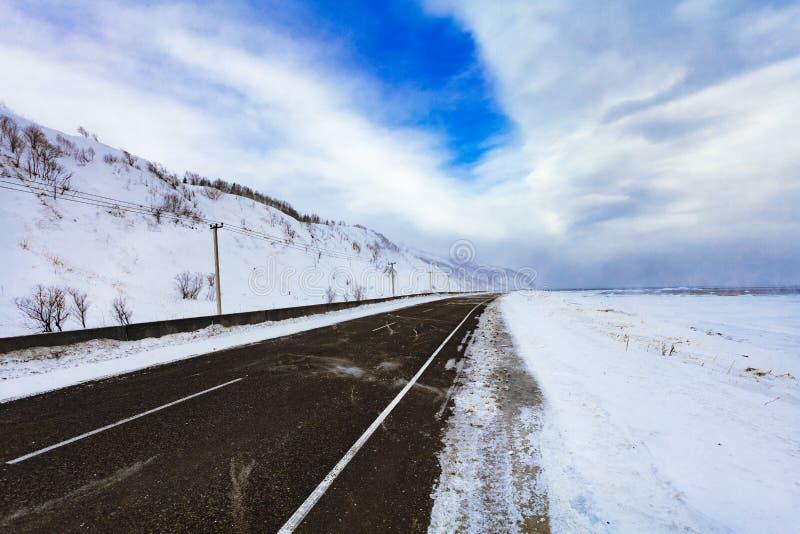 Carretera de asfalto del invierno en las montañas cubiertas con nieve en día cubierto Paisaje del invierno El concepto de liberta fotos de archivo
