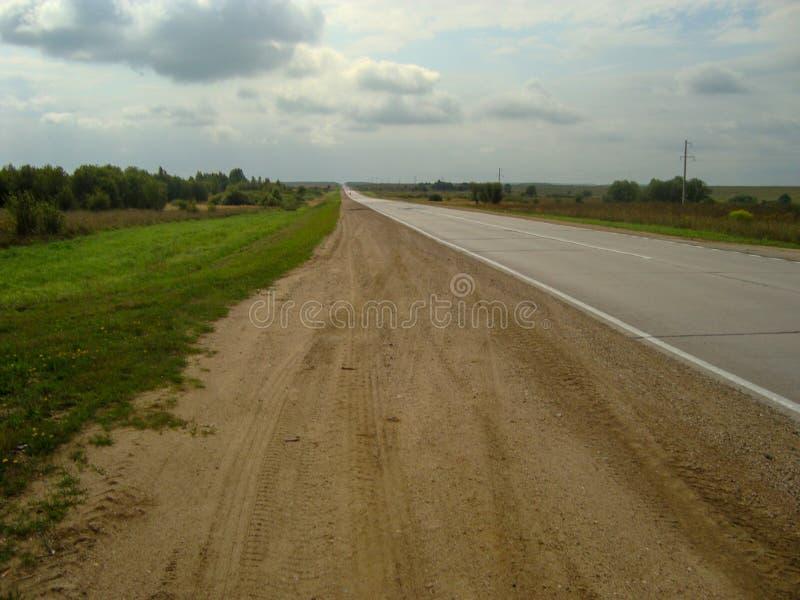 Carretera de asfalto directa a través del campo debajo del cielo, en el cual las nubes flotan imágenes de archivo libres de regalías