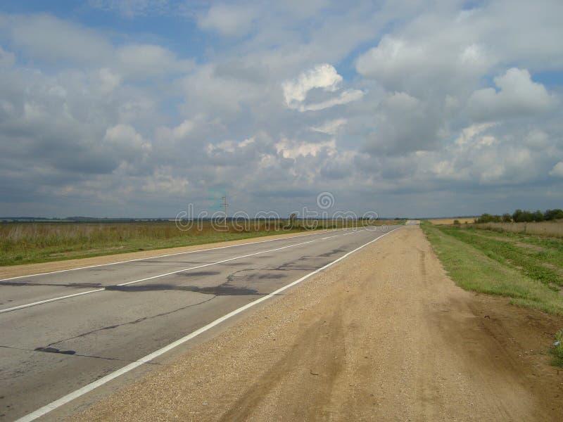 Carretera de asfalto directa a través del campo debajo del cielo, en el cual las nubes flotan fotografía de archivo