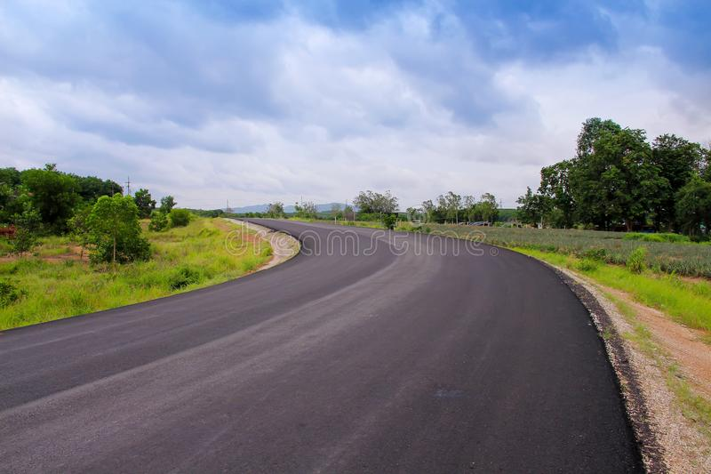 Carretera de asfalto en blanco larga con el árbol verde colorido, hierba en el lado en fondo del cielo azul y nublado blanco imagen de archivo