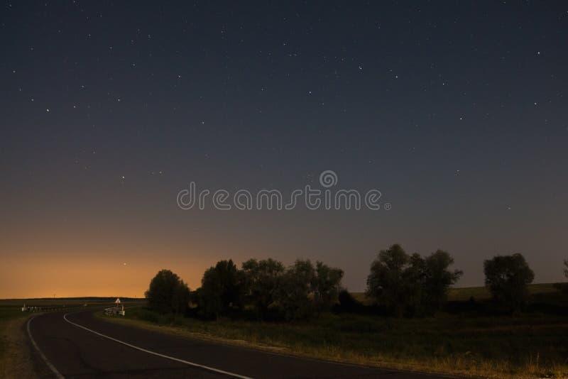 Carretera de asfalto en un paisaje en la noche con las estrellas en el cielo fotos de archivo libres de regalías
