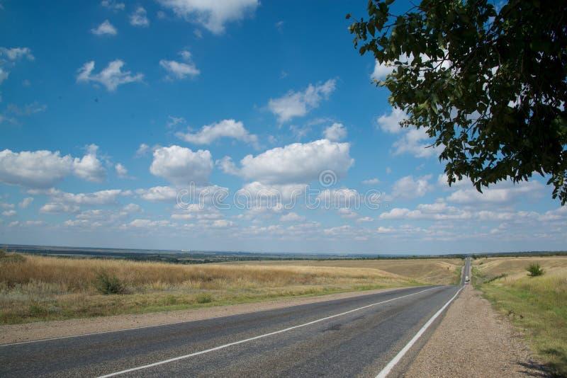 Carretera de asfalto que va al horizonte en un d?a de verano soleado imagenes de archivo